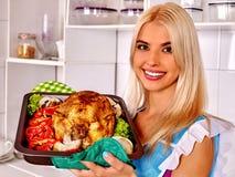 Kobieta kulinarny kurczak przy kuchnią zdjęcia royalty free