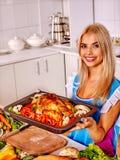 Kobieta kulinarny kurczak przy kuchnią fotografia stock