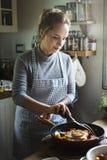 Kobieta kulinarny stek w kuchni fotografia stock