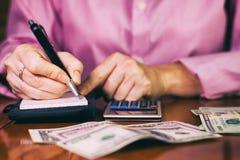 Kobieta liczy pieniądze i pisze rezultacie notatka fotografia stock