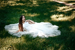 Kobieta lub dziewczyna, panna młoda w białej ślubnej sukni, siedzi na Obraz Stock