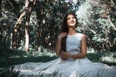 Kobieta lub dziewczyna, panna młoda w białej ślubnej sukni, siedzi na Obrazy Royalty Free