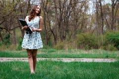 Kobieta lub dziewczyna w sukni z laptopem i hełmofonami szczęśliwymi w th, Obrazy Stock
