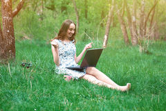 Kobieta lub dziewczyna w sukni z laptopem i hełmofonami, siedzimy dalej Fotografia Royalty Free