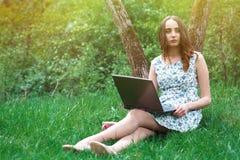 Kobieta lub dziewczyna w sukni z laptopem i hełmofonami, siedzimy dalej Fotografia Stock
