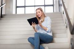 Kobieta lub uczeń z pastylka komputerem osobistym siedzi na schodkach Zdjęcia Royalty Free