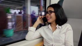 Kobieta mówi na telefonie komórkowym w lotnisko pociągu zbiory