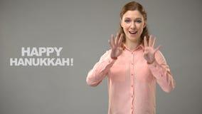 Kobieta mówi szczęśliwego Hanukkah w szyldowym języku, tekst na tle, komunikacja zbiory