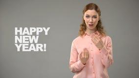 Kobieta mówi szczęśliwego nowego roku w szyldowym języku, tekst na tle, komunikacja zbiory