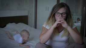 Kobieta męcząca z dzieciakiem, nieszczęśliwi nerwowi potomstwo matki chwyty przewodzi na tła dziecka lying on the beach na łóżku zbiory wideo