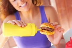 Kobieta Ma Mini hamburger Z musztarda kumberlandem obraz royalty free