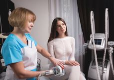 Kobieta ma procedurę masaż na nogach w aparat kosmetologii klinice Kobieta w specjalnym białym kostiumu dostaje anty Zdjęcie Stock