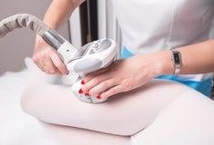 Kobieta ma procedurę masaż na nogach w aparat kosmetologii klinice Kobieta w specjalnym białym kostiumu dostaje anty Obraz Stock
