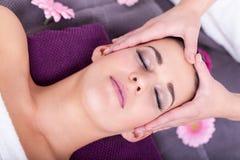 Kobieta ma relaksującego twarzowego masaż zdjęcie stock