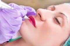 Kobieta ma stałego makeup na wargach w beautician salonie zdjęcia stock