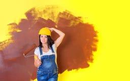 Kobieta malarz w budowa hełmie z farba rolownikiem zdjęcie stock