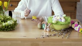 Kobieta maluje żółtego jajko na stole z Wielkanocnymi dekoracjami zbiory