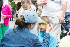 kobieta maluje chłopiec ` s twarz z kolorami, podczas świętowania Europa dzień Obrazy Royalty Free