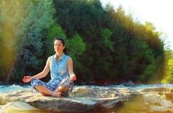Kobieta medytuje na brzeg rzeki Fotografia Royalty Free