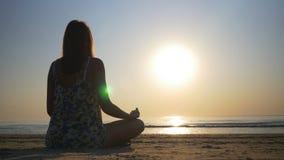 Kobieta medytuje na plaży w kierunku morza zdjęcie wideo