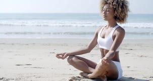 Kobieta medytuje na plaży w lotosowej pozyci zbiory wideo