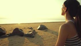 Kobieta medytuje na plaży w lotosowej pozyci Piękna plaża w zmierzchu zbiory