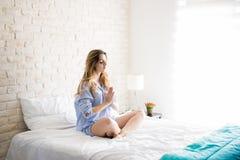 Kobieta medytuje w łóżku Zdjęcie Stock