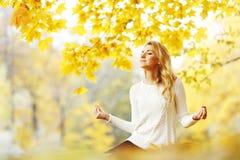 Kobieta medytuje w jesień parku Obraz Royalty Free