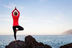 Kobieta medytuje w joga vrksasana drzewnej pozie zdjęcia stock