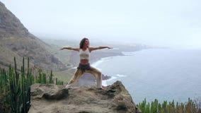 Kobieta medytuje w joga wojownika pozie przy oceanu, plaży i skały górami, Motywacja i inspiracyjny napad i zbiory