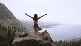 Kobieta medytuje w joga wojownika pozie przy oceanu, plaży i skały górami, Motywacja i inspiracyjny napad i zdjęcie wideo