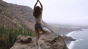 Kobieta medytuje w joga wojownika pozie przy oceanu, plaży i skały górami, Motywacja i inspiracyjny napad i zbiory wideo