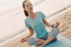 Kobieta medytuje w lotosowej pozyci na brzeg Fotografia Royalty Free