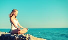 Kobieta medytuje w lotosowy joga na plaży Fotografia Royalty Free