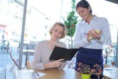 Kobieta menu przyglądająca kelnerka bierze rozkaz restaurację obrazy stock