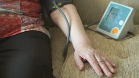 Kobieta mierzy arterialnego naciska używać tonometer zdjęcie wideo