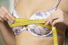 Kobieta Mierzy Jej stanika rozmiar Z taśmy miarą Obraz Stock