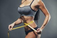 Kobieta mierzy jej talię z żółtą taśmą Zdjęcie Stock