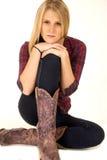 Kobieta model jest ubranym kowbojskich butów ręki na kolanach Zdjęcia Stock