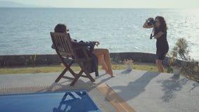 Kobieta modela pozy na deckchair dla żeńskiego fotografa zdjęcie wideo