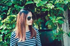 Kobieta modniś z okulary przeciwsłoneczni mody stylu stylu życia pojęciem, jest ubranym czarny i biały pasiastą koszulkę Zdjęcie Stock