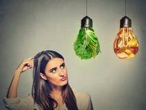 Kobieta myśleć przyglądającą przy szybkiego żarcia i zieleni warzywami kształtującymi jako żarówka up zdjęcie royalty free