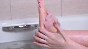 Kobieta myje jej stopę rękami w łazience Stawia pętaczkę pieszo, stopa w górę zbiory wideo
