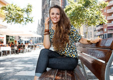 Kobieta na ławce nie daleko od Sagrada Familia opowiada wiszącą ozdobę Obraz Stock