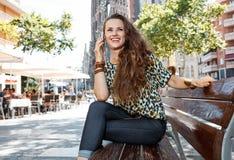 Kobieta na ławce nie daleko od Sagrada Familia opowiada wiszącą ozdobę Zdjęcia Royalty Free