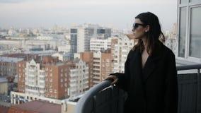 Kobieta na balkonie w tle miasto zdjęcie wideo