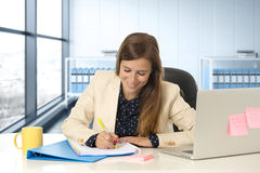 Kobieta na jej 30s przy biurowym działaniem przy laptopu biurkiem bierze notatki Obraz Royalty Free