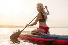 Kobieta na paddle desce przy zmierzchem zdjęcia royalty free