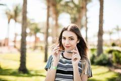 Kobieta na palma ogródzie dostaje puszków okulary przeciwsłonecznych od oczu i spojrzenia przy kamerą, lata powołanie Zdjęcie Royalty Free