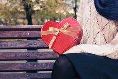 Kobieta na parkowej ławce z sercem kształtował pudełko Fotografia Stock